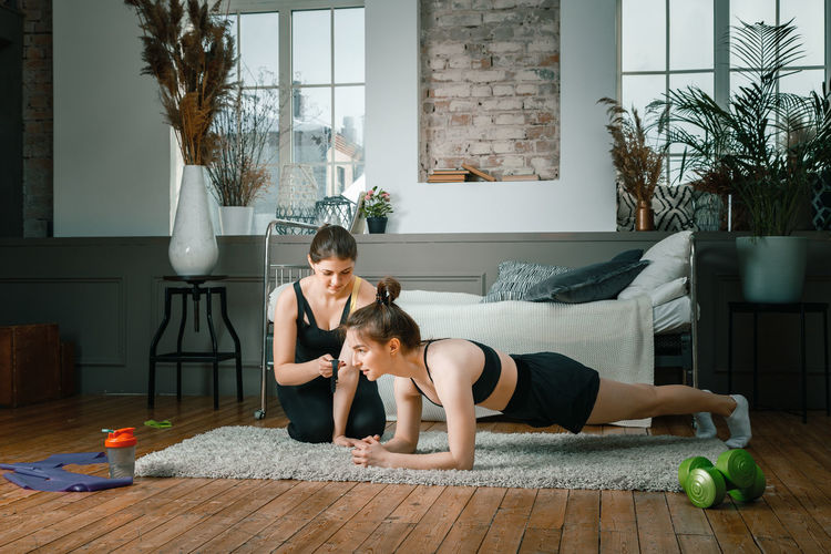 . home workout with a friend, the trainer monitors the plank time on the stopwatch