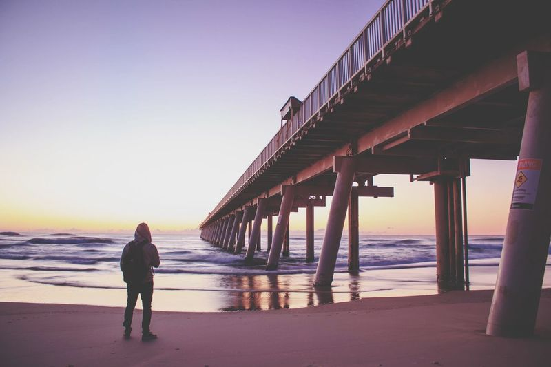 Rear view of man standing at beach by bridge against clear sky