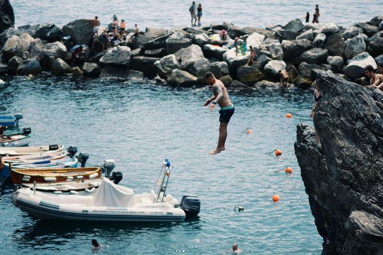 People on rocks by sea