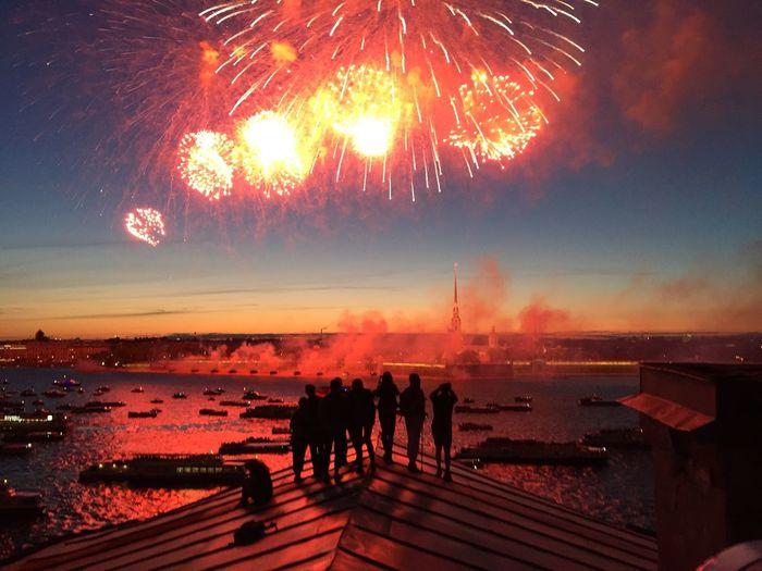 Silhouette people looking at firework display