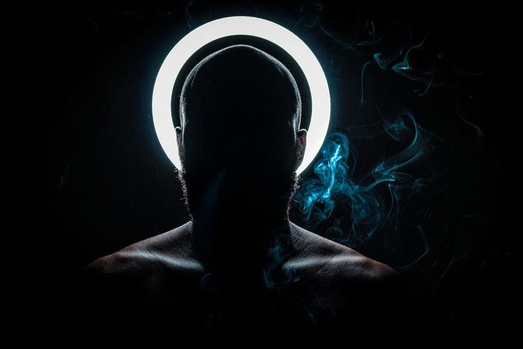 Shirtless man smoking cigarette against black background
