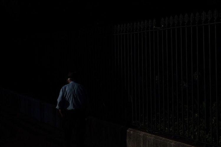 Rear view of man walking in dark room