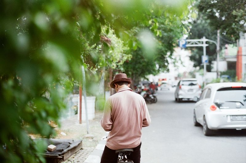 Rear view of man walking on street in city