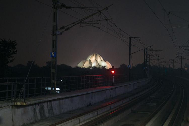 Railroad station platform against sky at night