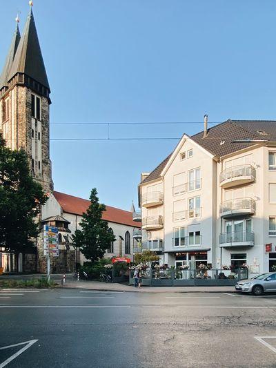Buildings by street against blue sky