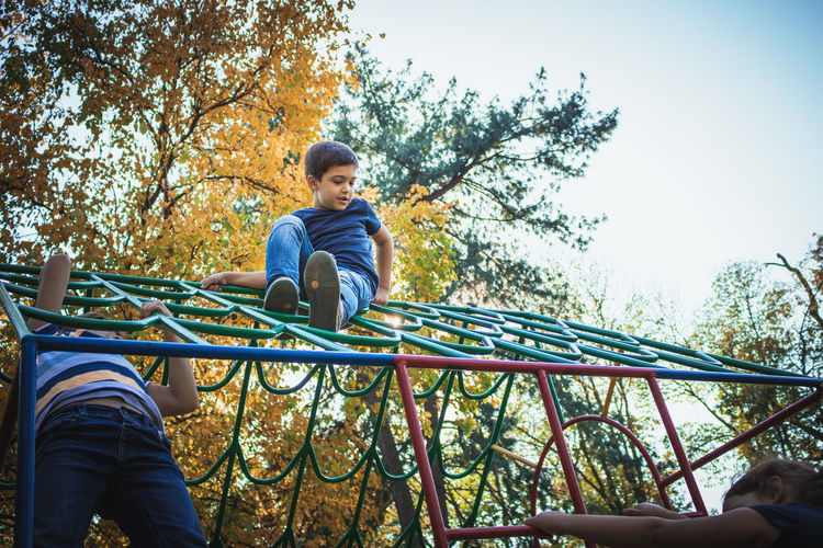 Low angle view of siblings playing on outdoor play equipment
