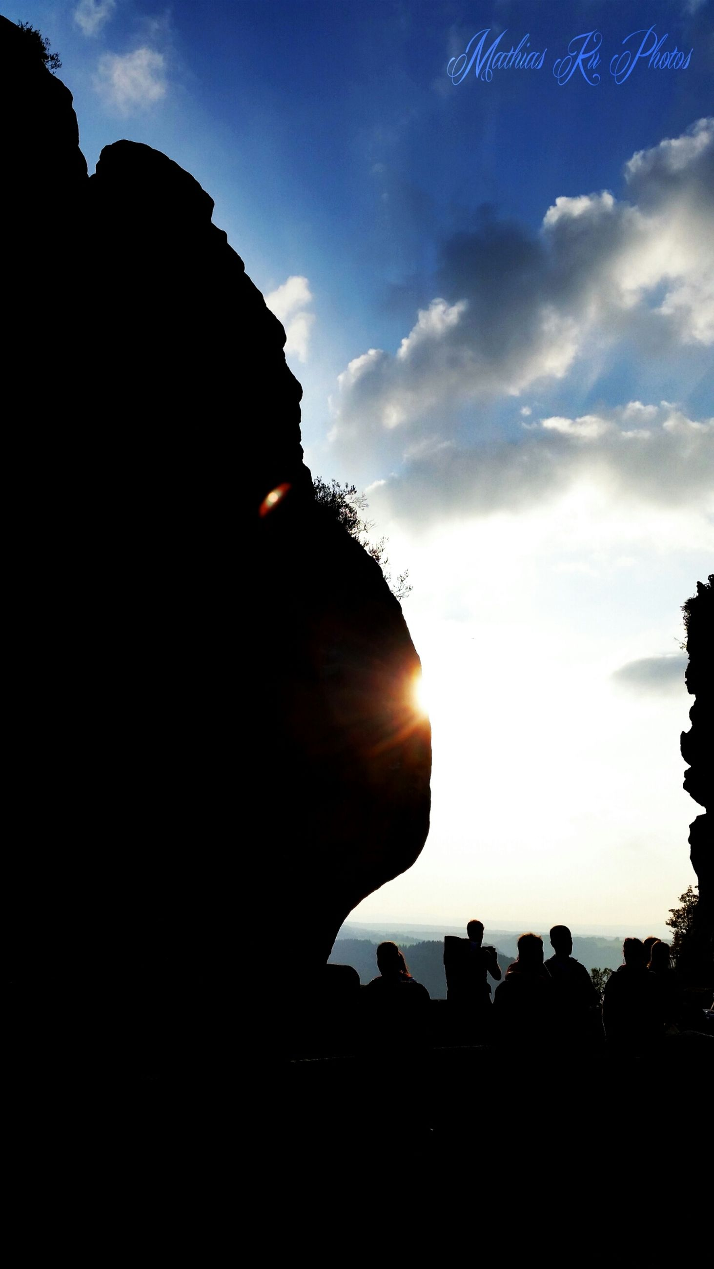 silhouette, sky, sunset, sun, building exterior, built structure, cloud - sky, architecture, sunlight, sunbeam, low angle view, cloud, mountain, nature, dark, scenics, lens flare, dusk, beauty in nature, outdoors