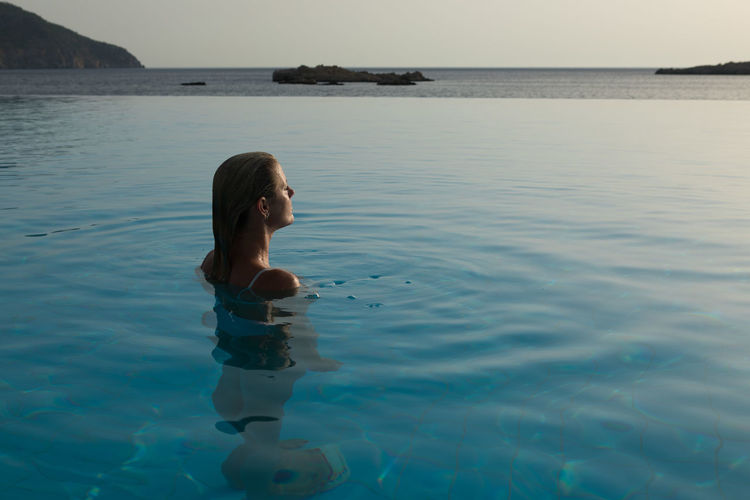 High angle view of woman in infinity pool against sea
