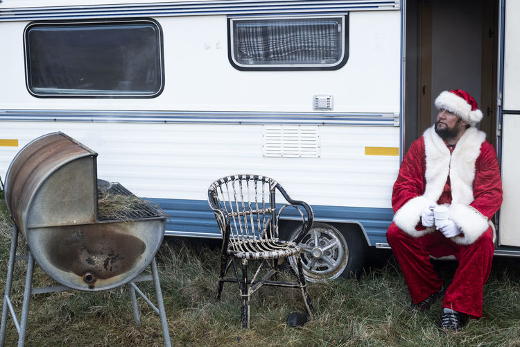 Traditional authentic style Santa Claus sitting in his old caravan with barbecue in Iceland Barbecue Santa Claus Caravan Christmas Festivity Holidays Home Lifestyle Merry Christmas! Peaceful Traditional Sitting Iceland Authentic Touching Winter Chair Man Father Celebrating Joyful Relaxing Red White Beard