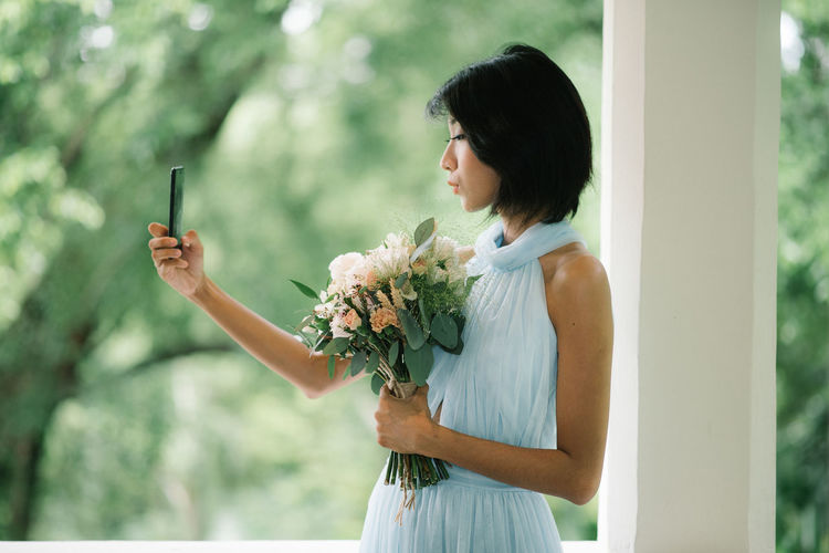 Beautiful young woman taking selfie while holding flower bouquet