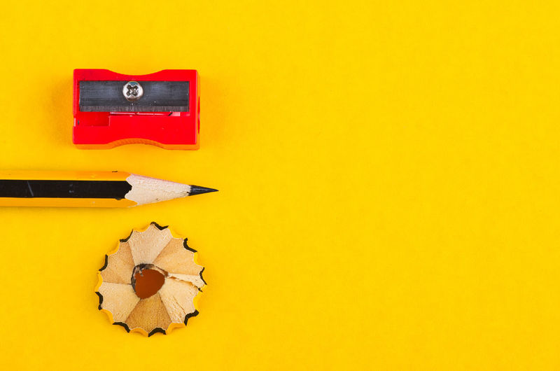 pencil with it shavings and sharpener over yellow background Yellow Indoors  No People Still Life Copy Space Close-up Studio Shot Red Colored Background Orange Color High Angle View Creativity Paper Table Choice Wall - Building Feature Directly Above Wood - Material Art And Craft Metal