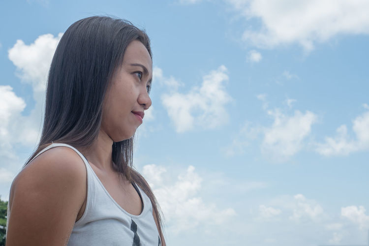 Portrait of a young woman looking away against sky