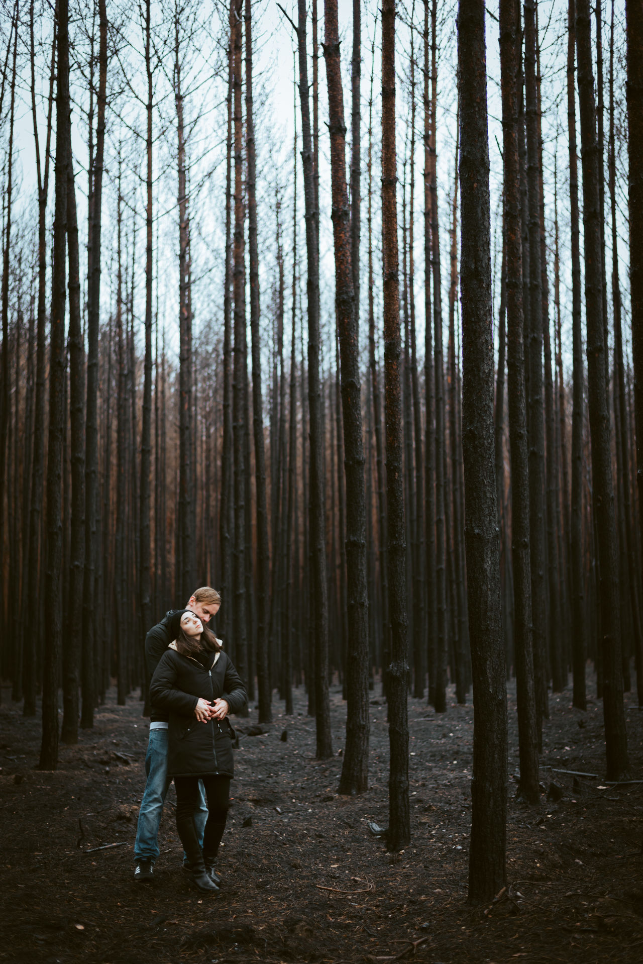 FULL LENGTH OF MAN STANDING BY TREE IN FOREST