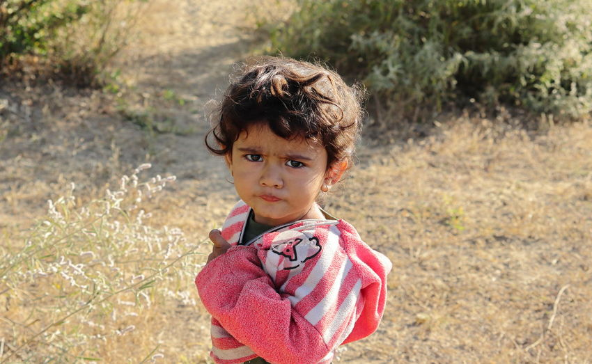 A small boy of indian origin looking at the camera angrily