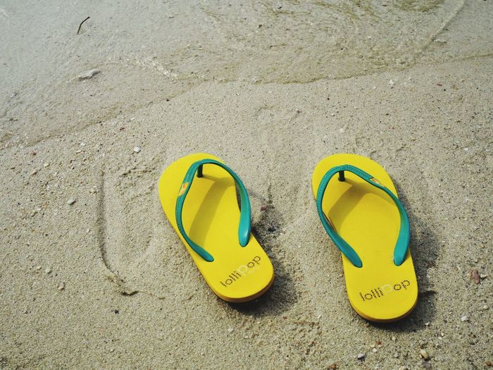 High angle view of yellow shoes on sand