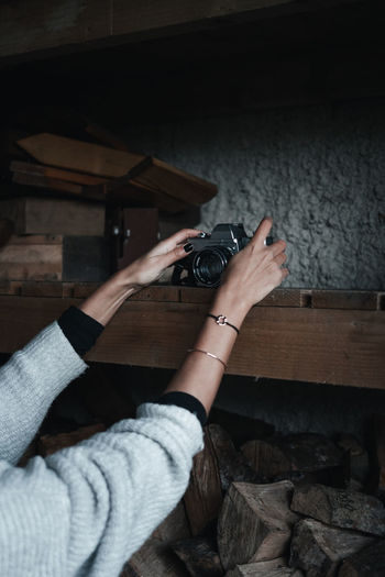 Cropped hands of woman putting camera on shelf
