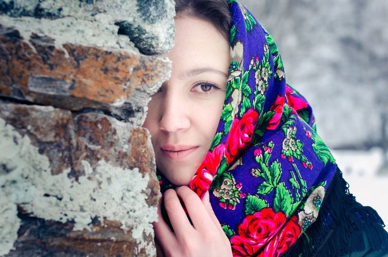 Portrait of beautiful young woman wearing scarf while standing by wall