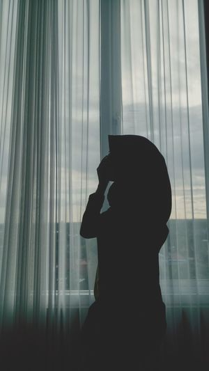 Silhouette woman standing by curtain