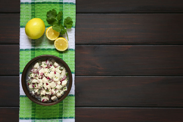 Chilean Ceviche made of Southern Ray's bream fish (lat. Brama Australis, Spanish Reineta), onion, garlic and cilantro marinated in lemon juice. Photographed overhead on dark wood with natural light. Brama Australis Chile Chilean  Copy Space Homemade Raw Seafood Snack Appetizer Cebiche Ceviche Chilean Food Cilantro Coriander Fish Food Fresh Fruit Lemon Lemon Juice Marinated Onion Raw Food Reineta Uncooked