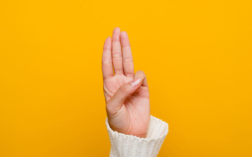 Close-up of woman hand over yellow background