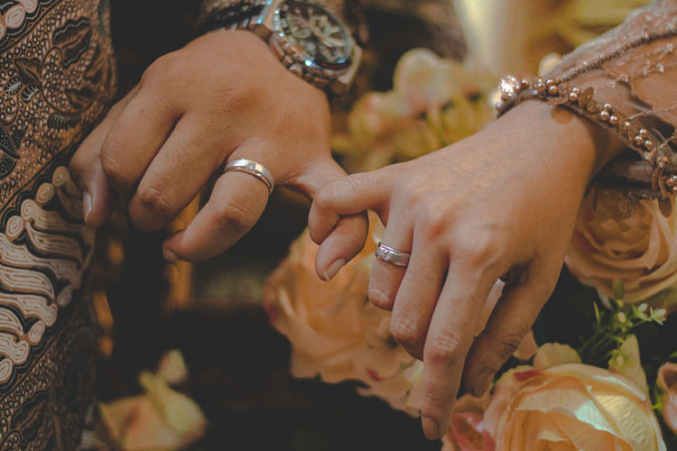 Midsection of couple hooking little finger during wedding ceremony