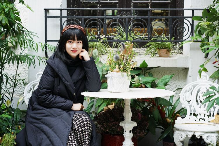 Portrait of woman sitting on potted plant