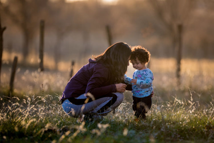 Mother With Daughter Crouching On Field During Sunset