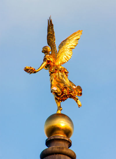 Low angle view of angel statue against clear blue sky