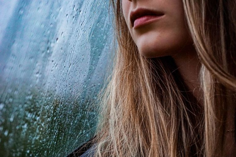 Close-up portrait of a beautiful woman in rainy day