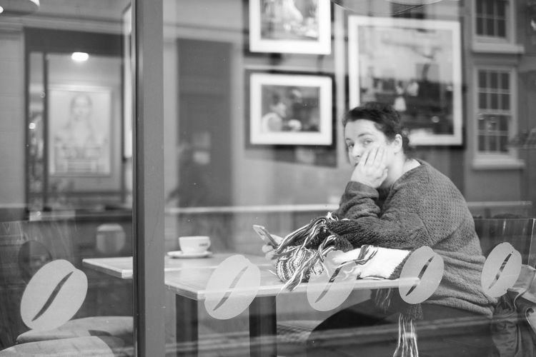 One Person Sitting Adult Lifestyles Real People Women Table Seat Cafe Window Females Reflection Beautiful Woman Communication Indoors  Chair Looking Contemplation Focus On Foreground Store EyeEm Streets Eyeem Streetphotography