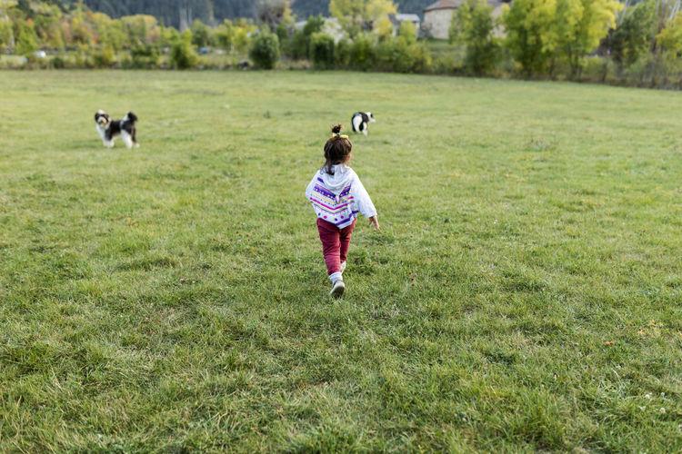 Full length of girl running on field