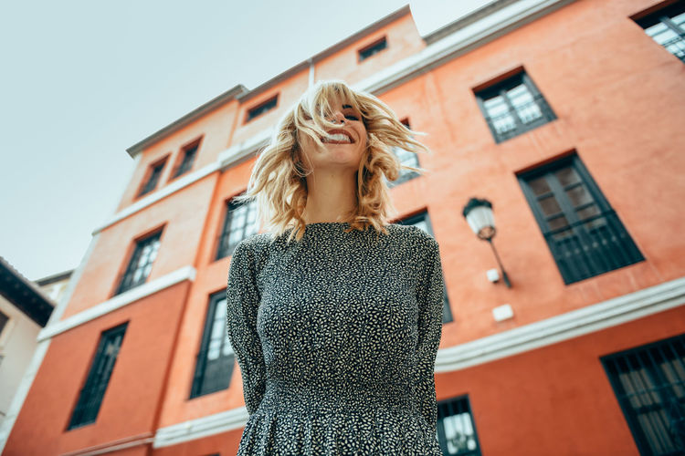 Happy young woman with moving hair in urban background. Blond girl, wavy hairstyle, wearing casual clothes in the street. Building Exterior Built Structure Architecture Blond Hair Hair Building Women One Person Low Angle View Lifestyles Standing Adult Leisure Activity Hairstyle Day Real People Young Women Focus On Foreground Long Hair Outdoors Warm Clothing Beautiful Woman