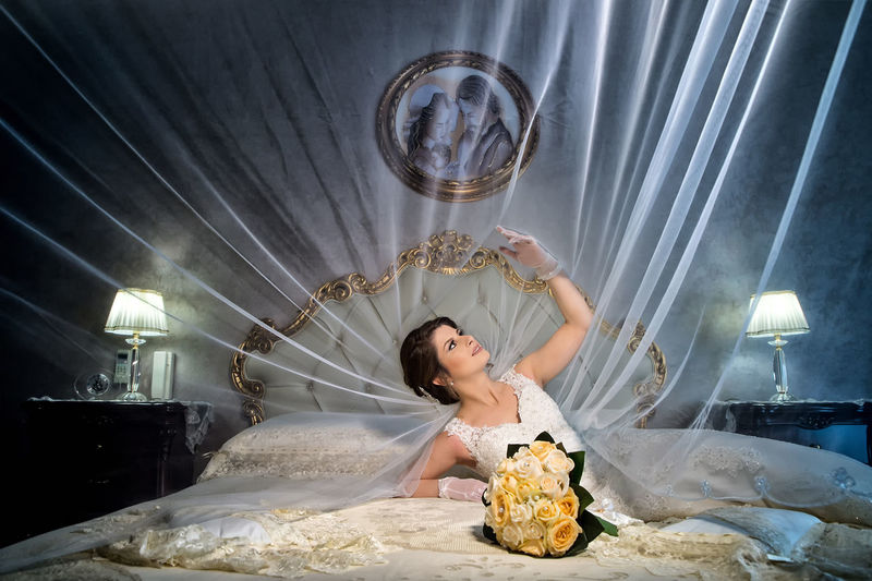 Bride Lying With Bouquet On Bed At Illuminated Home