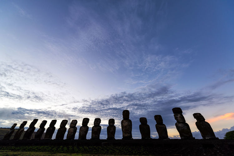 Low angle view of moai at ahu tongariki against sky during sunset