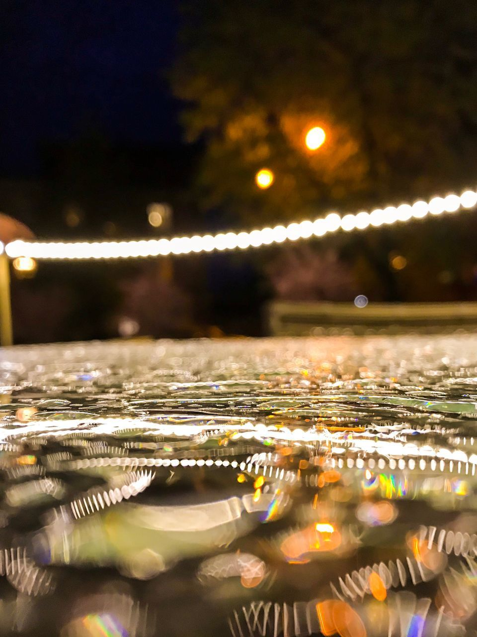 illuminated, night, water, selective focus, no people, glowing, lighting equipment, nature, close-up, outdoors, reflection, wet, motion, surface level, drop, sky, light - natural phenomenon, waterfront, beauty in nature, raindrop