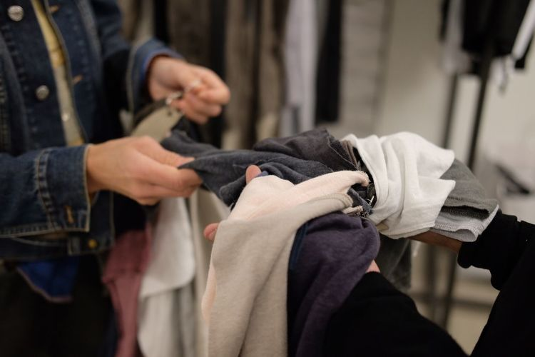 Midsection of salesman showing clothes to customer at store