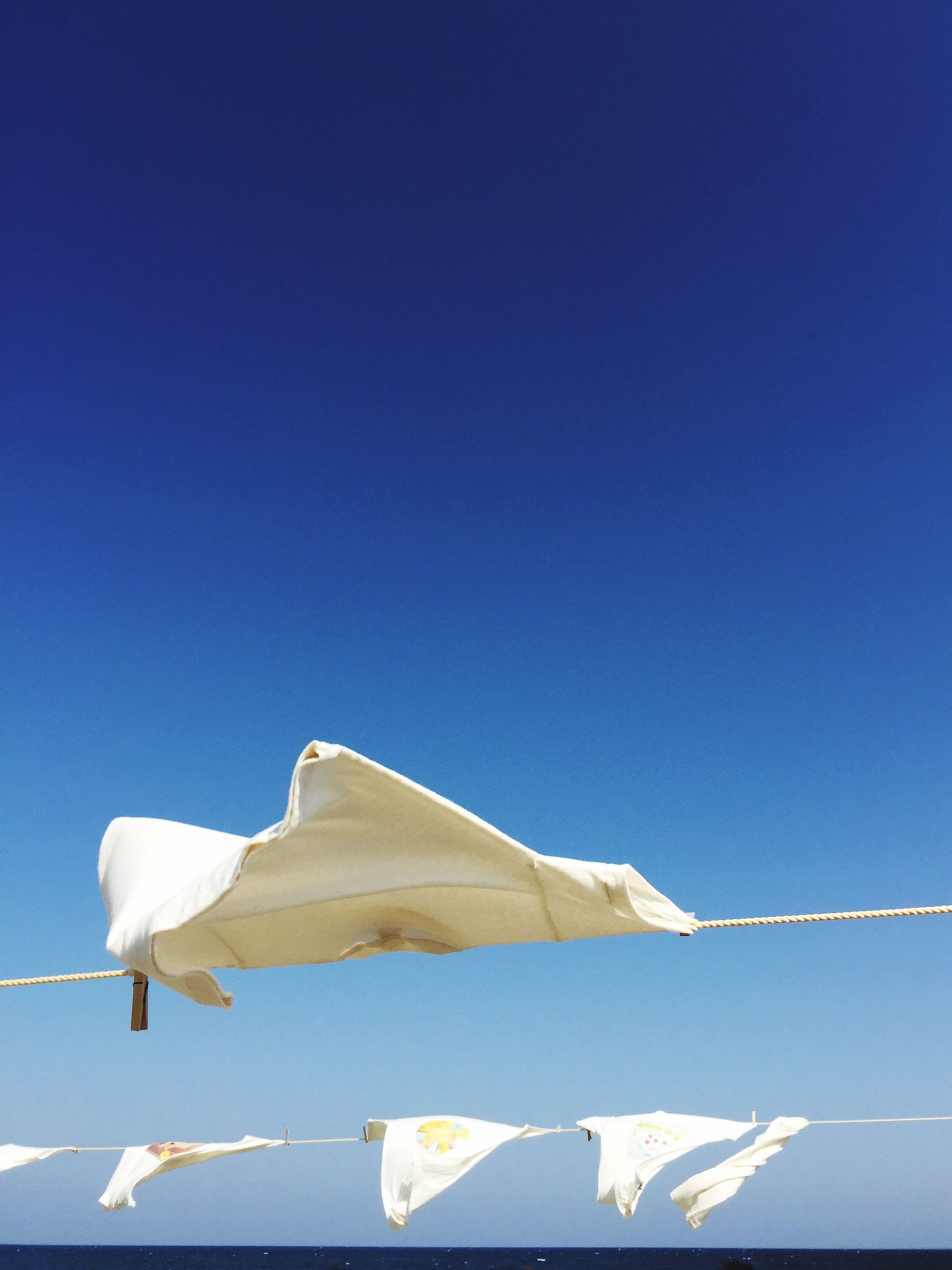 blue, low angle view, clear sky, white color, copy space, white, bird, no people, day, sunlight, outdoors, sky, nature, flag, fabric, hanging, high section, built structure, roof, part of