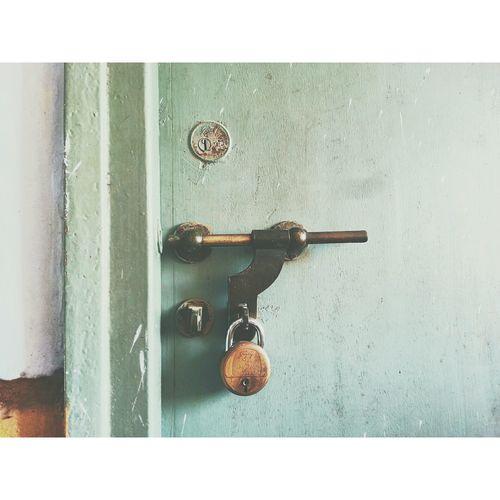 Padlock On Latch Of Closed Door