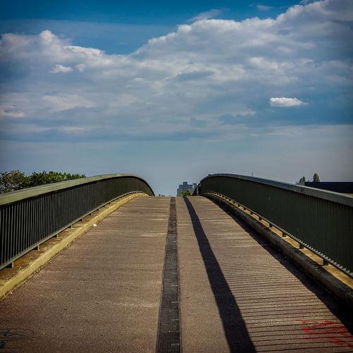 Surface level of footbridge over road against sky