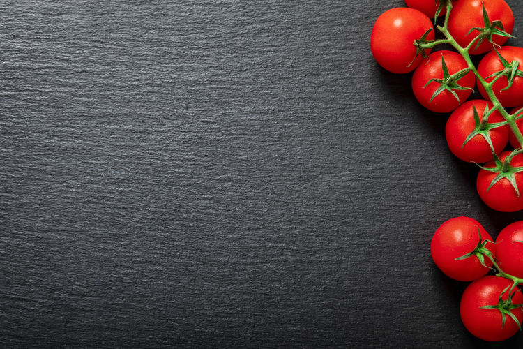 Background of fresh tomatoes on the vine on a black slate stone Tomato Fruit Red Food And Drink Vegetable Freshness Food Healthy Eating Wellbeing Directly Above High Angle View Table Close-up Black Background Healthy Lifestyle Ripe Vine Background Cooking Salad Copy Space Slate Stone Red Juicy