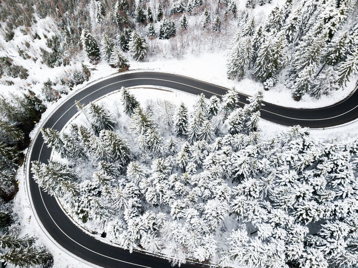 Aerial view of winding road in high mountain pass trough pine woods snowed