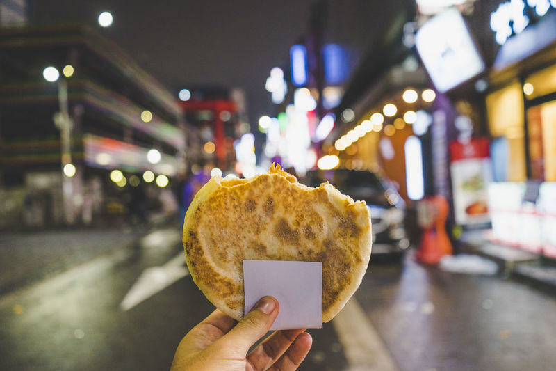 Cropped hand holding bread in city at night