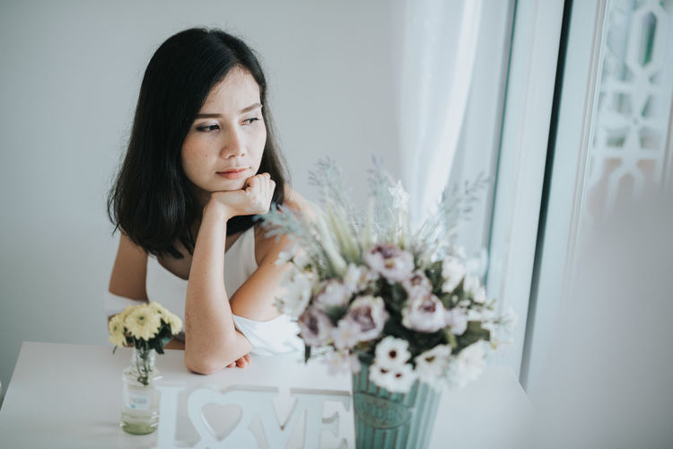Woman Sitting By Flowers At Home