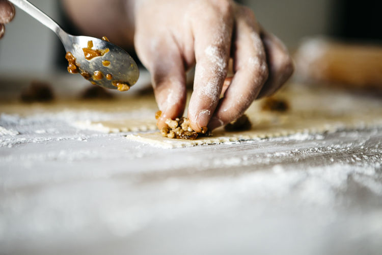 Cropped hand of man preparing food on table in kitchen