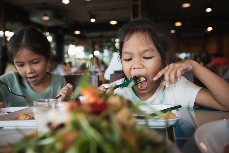 Cute girl having food in restaurant