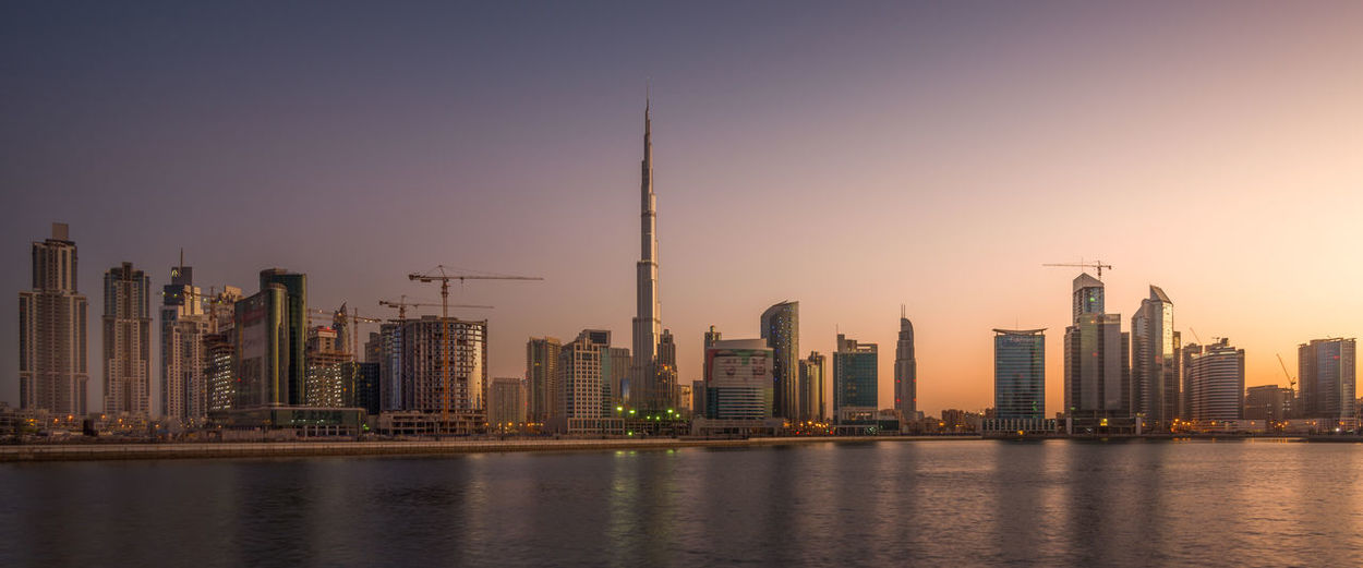 Sea against burj khalifa amidst towers against sky at sunset