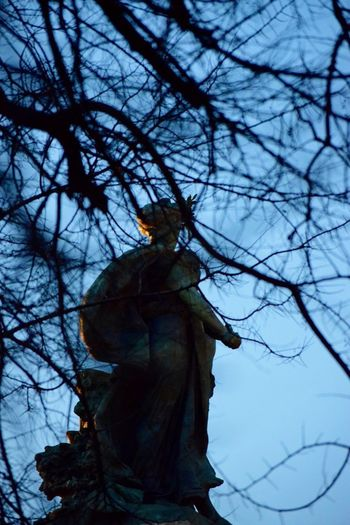 Low angle view of a statue against bare tree