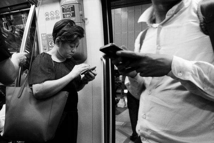 modern communication Communication Android Smartphone Streetphotography City Life Citizen Commuter Train Commuting City Life City Gate Blackandwhite Photography Storytelling Reflection Close-up