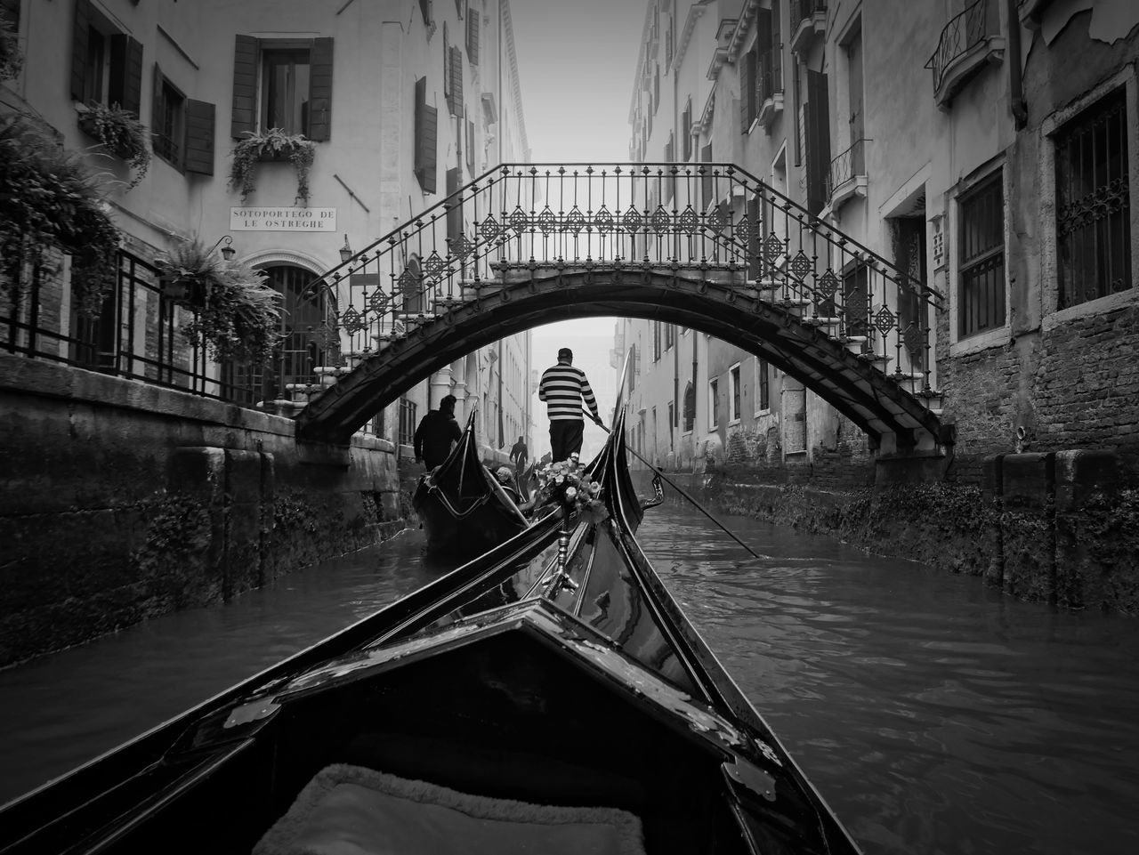 canal, gondola - traditional boat, architecture, built structure, water, building exterior, transportation, gondola, gondolier, nautical vessel, bridge - man made structure, day, mode of transport, travel destinations, outdoors, real people, men, rowing, city, people