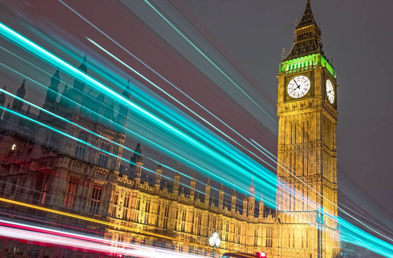 Low angle view of multi colored light trails by illuminated big ben and houses of parliament at night